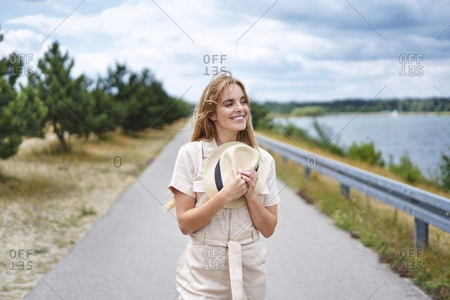 Smiling woman holding hat on rural road at the lakeside