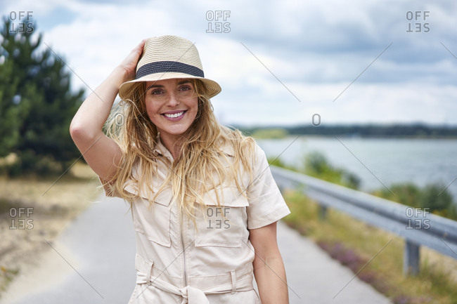 Portrait of smiling woman on rural road at the lakeside