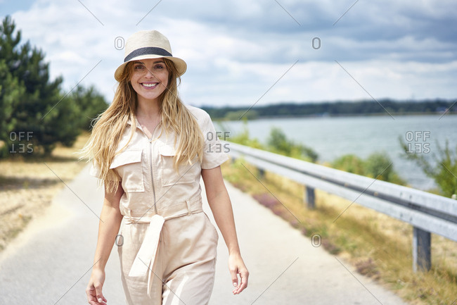 Portrait of smiling woman walking on rural road at the lakeside