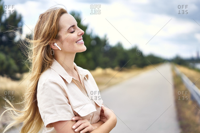 Smiling woman with wireless earphones and closed eyes in nature