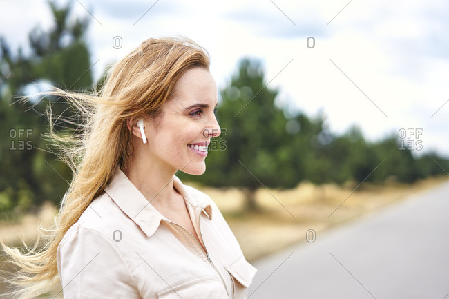 Portrait of happy woman with wireless earphones in nature