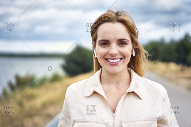 Portrait of smiling woman with wireless earphones in nature