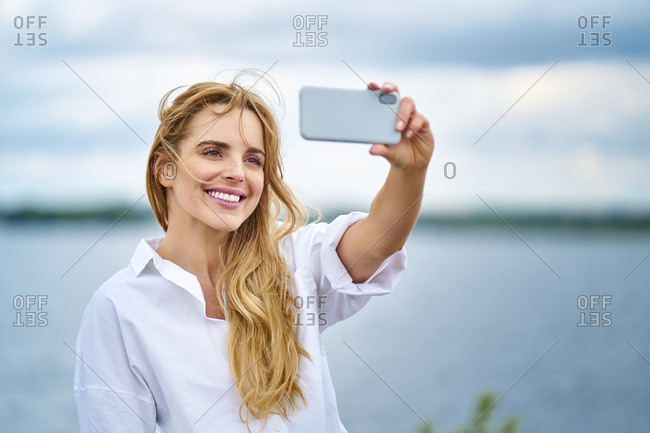 Happy woman taking selfie with smartphone at the lakeside