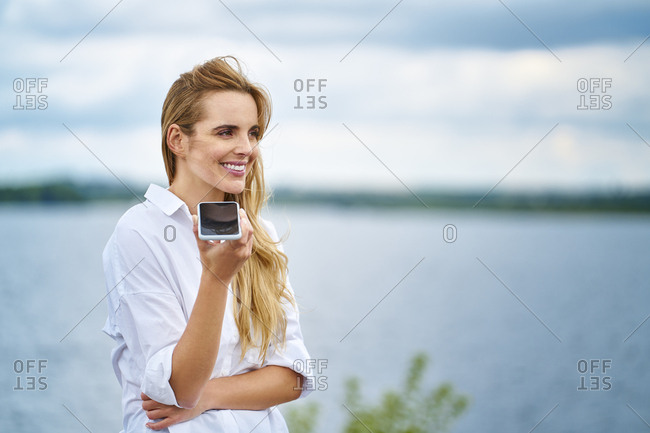 Happy woman using cell phone at the lakeside