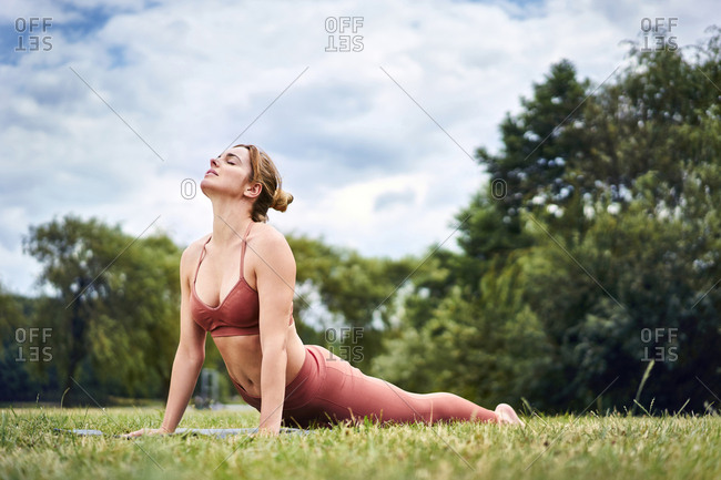 Woman doing cobra pose during yoga training in the park