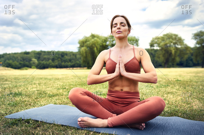 Woman practicing yoga in park meditating