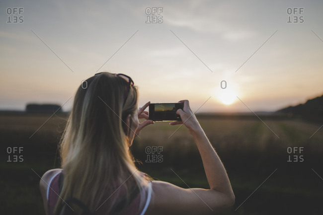 Woman taking a photo of sunset with her smartphone