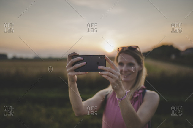 Woman taking a selfie at sunset