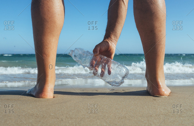 Man standing at seashore picking up empty plastic bottle- close-up