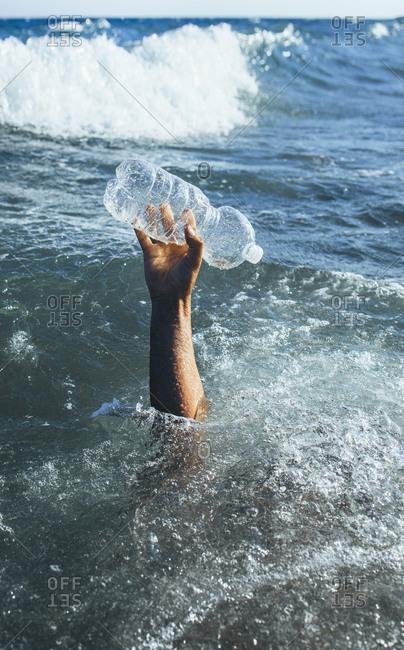 Man's hand picking up plastic bottle