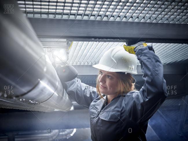 Craftswoman wearing hard hat working at pipe