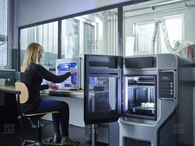 Female technician checking 3D printer with turbine wheel being printed