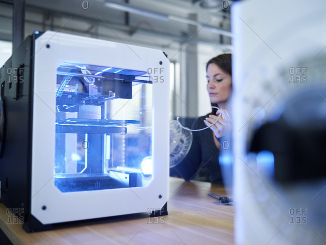 Woman and 3D printer on table