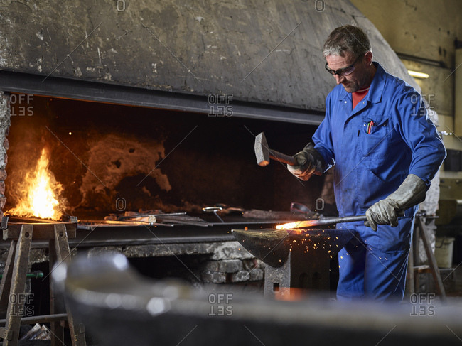 Blacksmith hammering hot iron