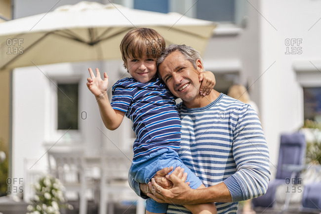 Portrait of father carrying son in garden