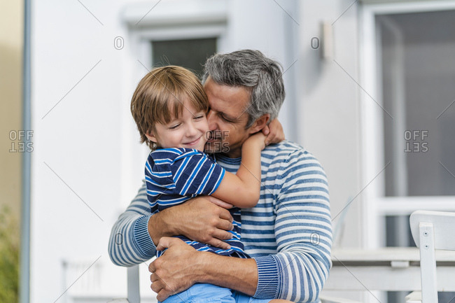 Father and son cuddling in garden