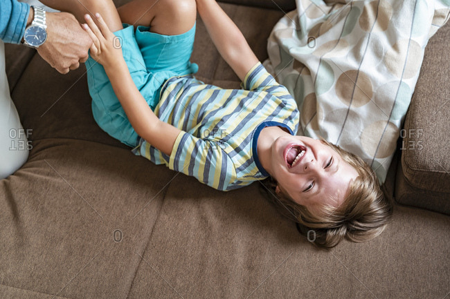 Playful father and son on couch at home