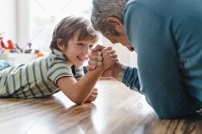 Father and son lying on the floor at home arm wrestling