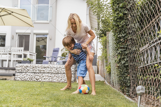 Happy mother and son playing football in garden