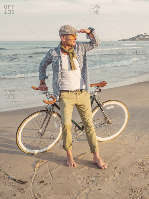 Barefoot man standing with Fixie bike on the beach looking at distance