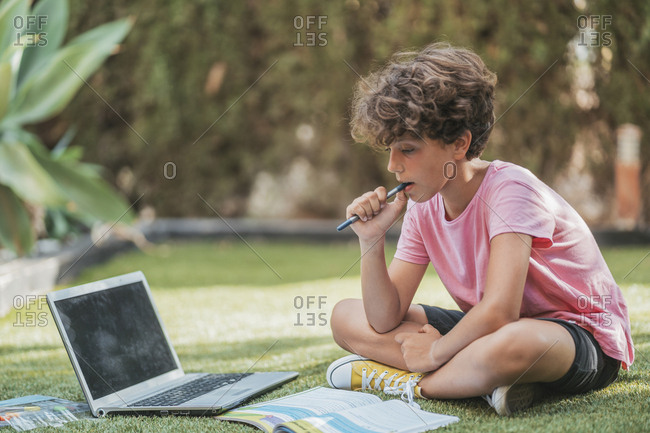 Boy doing homework in garden with laptop and workbook