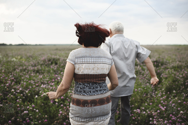 Back view of senior couple running on flower meadow