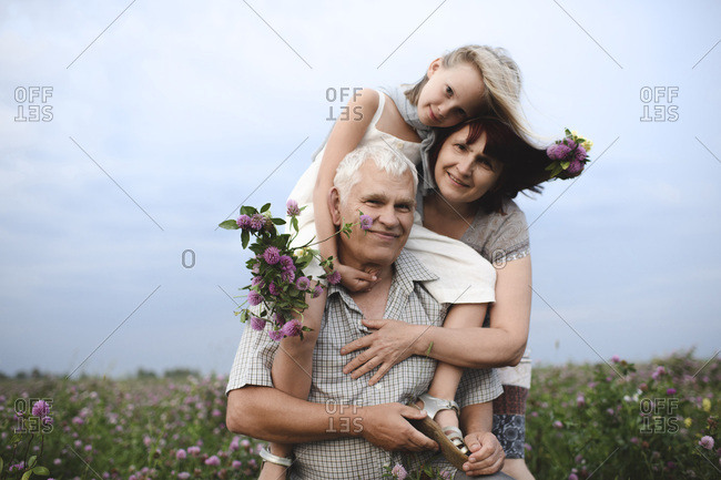 Portrait of little girl and her grandparents with picked flowers in nature