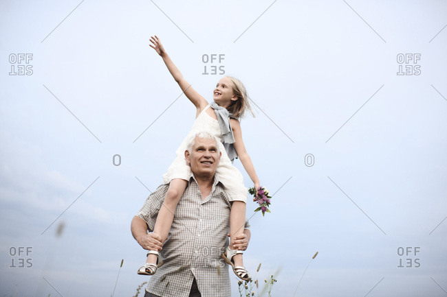Senior man carrying happy granddaughter on his shoulders in nature