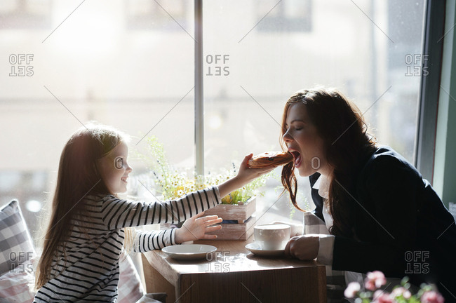 Smiling girl giving a peace of pie to her mother in cafe