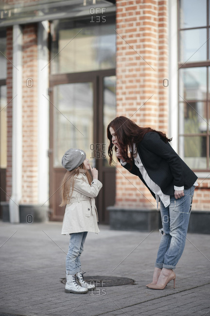 Pregnant woman with her daughter shushing