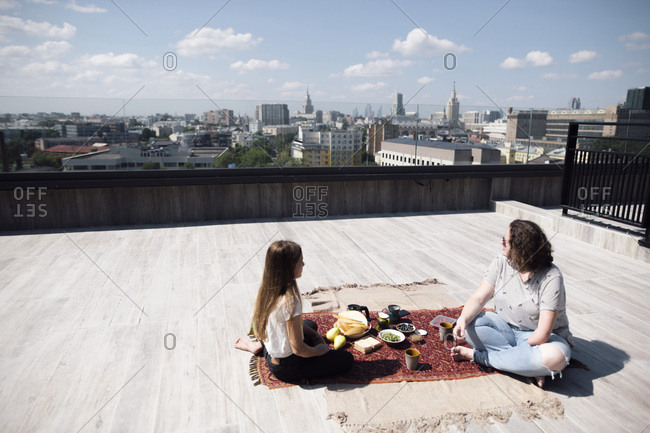 Woman with below-elbow amputation and girl having a healthy meal on the roof
