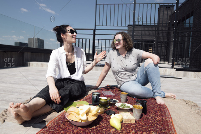Woman with below-elbow amputation with her friend having a healthy meal on the roof