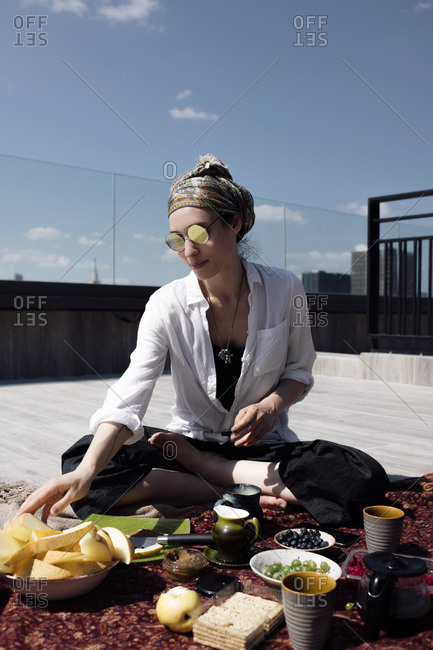 Stylish woman with sunglasses having a healthy meal on the roof