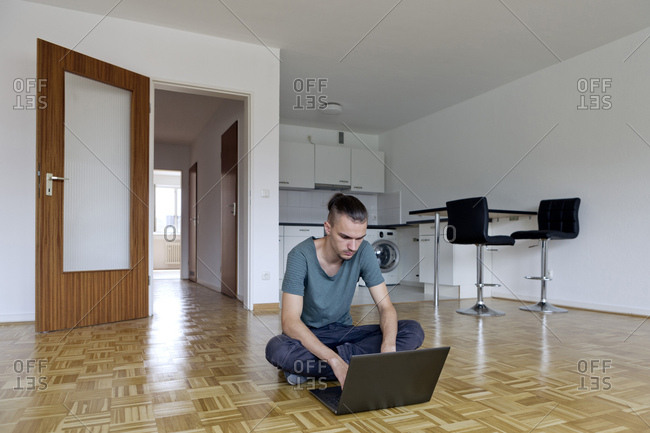 Young man sitting in an empty apartment using his laptop