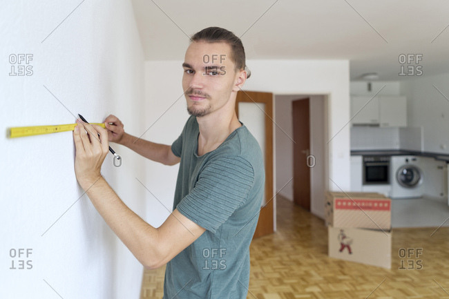 Young man measuring the wall in an empty apartment