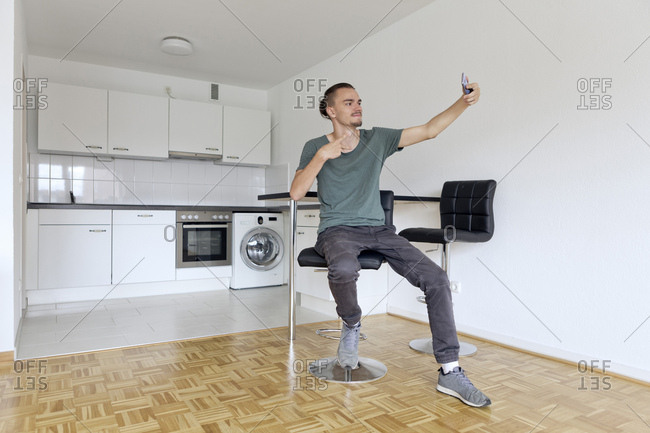 Young man taking a selfie with his smartphone in an empty apartment
