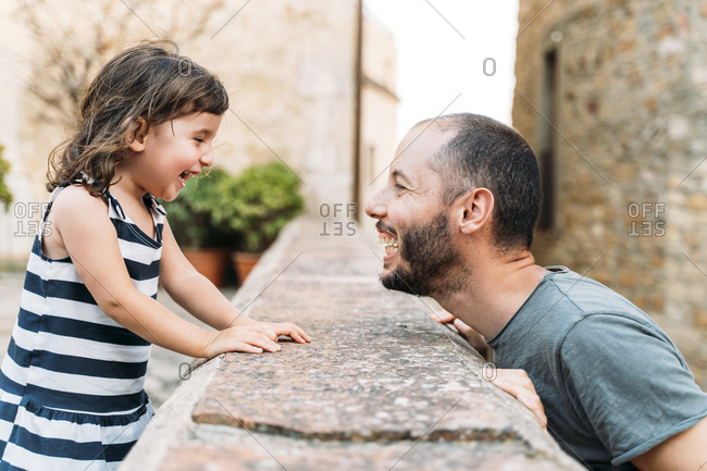 Happy little girl and father playing together outdoors