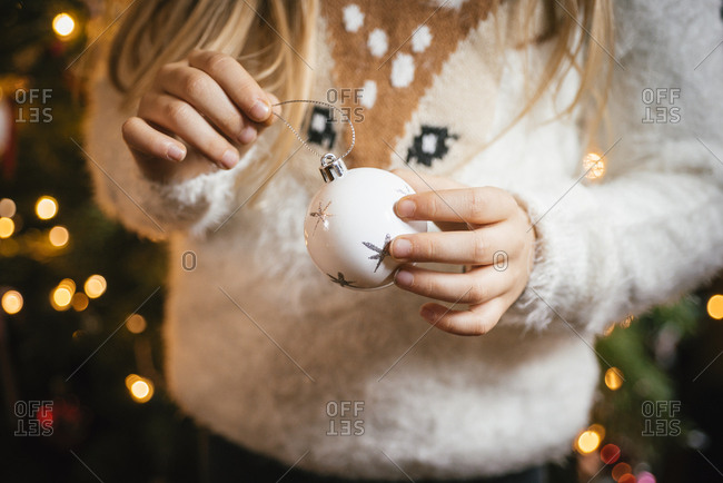 Decorating the christmas tree- girl holding a white bauble with silver stars
