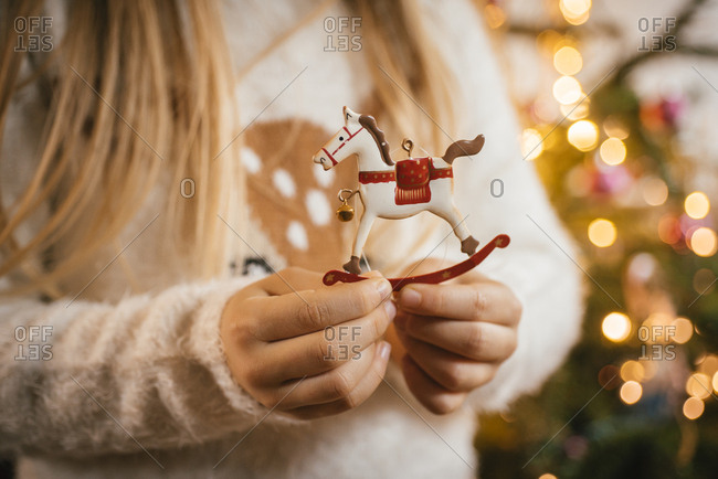 Decorating the christmas tree- girl holding an ornamental metal rocking horse