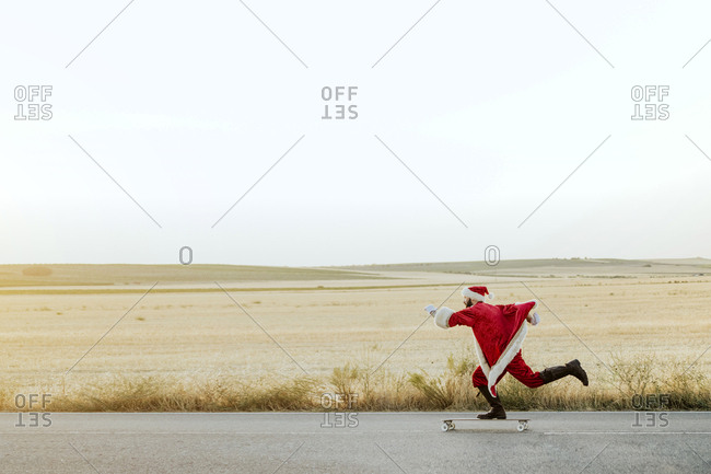 Santa Claus riding on longboard on country road