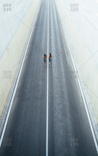 Top view of two sporty twin sisters running on a street