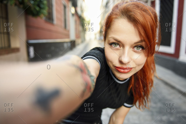 Selfie portrait of red-haired woman in the city