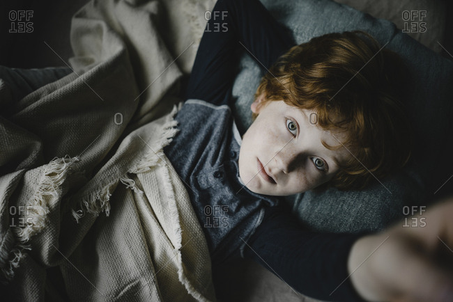 Portrait of redheaded boy lying on couch looking up