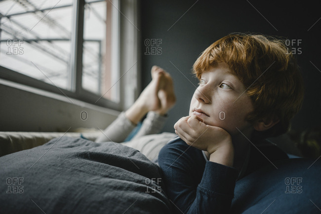 Portrait of redheaded boy lying on couch out of window
