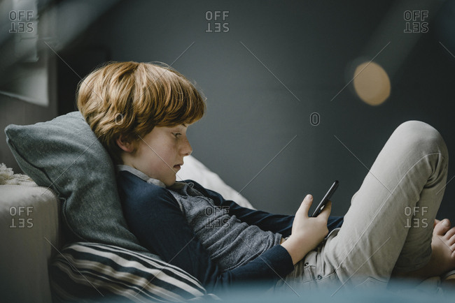 Redheaded boy lying on couch looking at cell phone