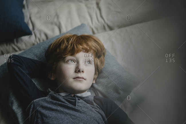 Portrait of redheaded boy lying on couch looking at distance