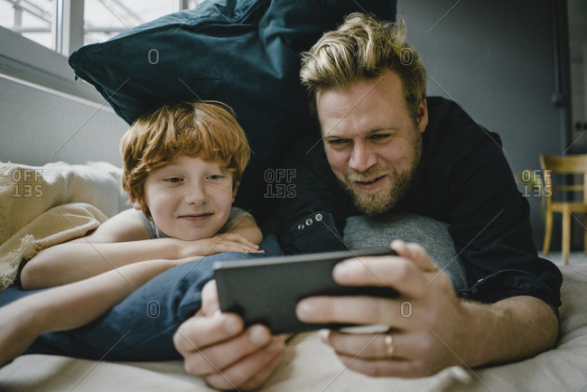 Portrait of father and son lying on couch looking at cell phone