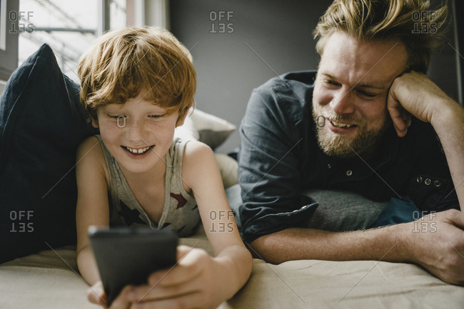 Portrait of happy father and son lying together on couch looking at cell phone