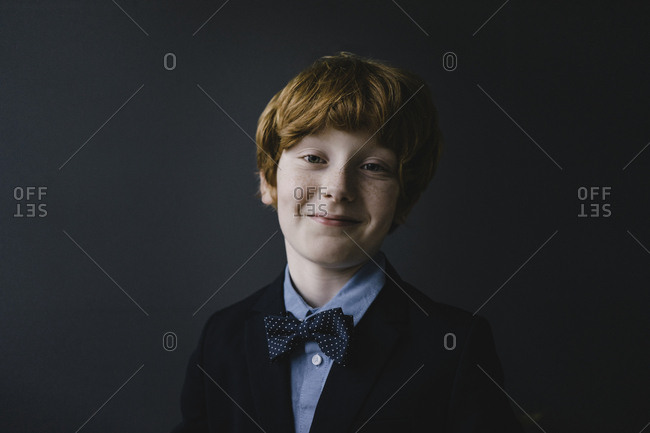 Portrait of smiling redheaded boy wearing bow tie