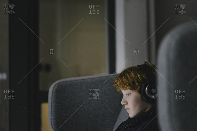 Profile of redheaded boy with headphones on wingback chair